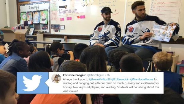 Manitoba Moose players reading to a class