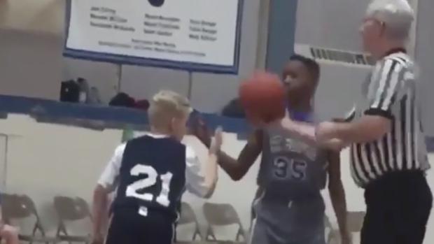 Young basketball player wins jump ball against taller ...